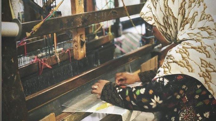Orang sedang menenun dari bahan sutera