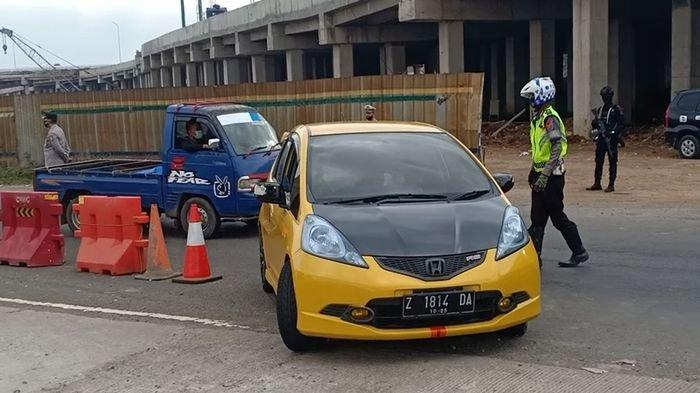 Petugas meminta pengandara yang diduga pemudik memutar arah setelah keluar Gerbang Tol Cileunyi, Rabu (12/5/2021).