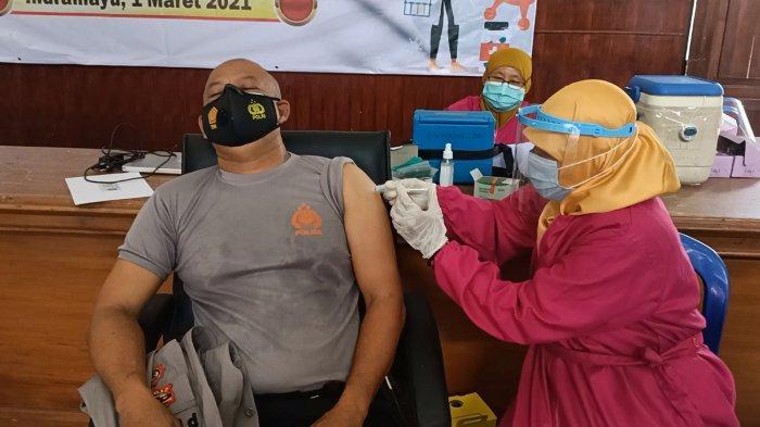 Seorang anggota Polres Indramayu memejamkan mata seolah pasrah saat disuntik vaksin Covid-19.