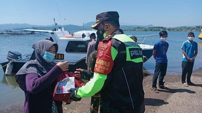 Anggota Kepolisian Resor Sumedang membagikan paket sembako kepada para pekerja jaring apung di Waduk Jatigede, Sumedang, Minggu (25/7/2021).