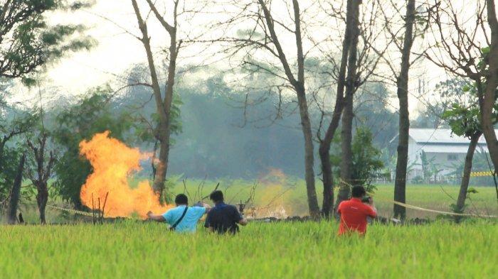 Warga saat melihat semburan api di Desa Sukaperna, Kecamatan Tukdana, Kabupaten Indramayu, Sabtu (3/4/2021).
