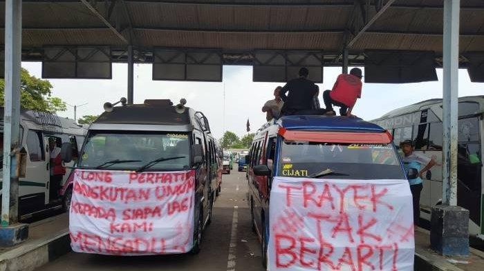 Sopir angkutan umum elf di Cianjur melakukan aksi protes di terminal Pasirhayam dengan membentangkan spanduk bertuliskan kritikan untuk mobil travel yang beroperasi di Cianjur, Rabu (6/10/2021).