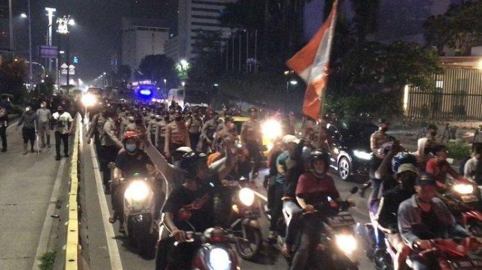 Personel Brimob Polri bersenjata lengkap dikerahkan untuk membubarkan massa pendukung klub sepak bola Persija Jakarta di kawasan Bundaran HI, Jakarta Pusat, Senin (26/4/2021) dini hari.