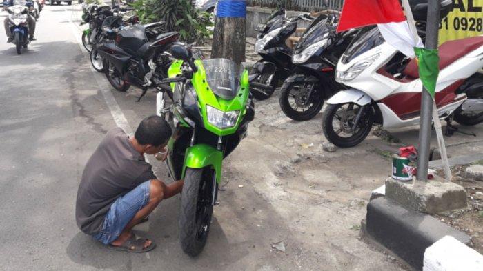 Tampak seorang pemilik motor bekas sedang membenahi dan merawat motor bekas miliknya.