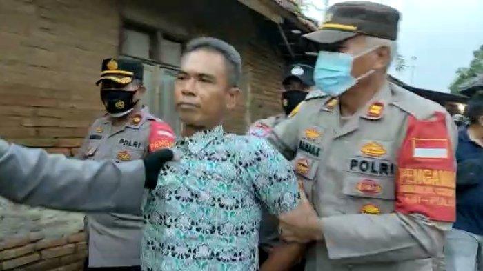 Polisi saat mengamankan seorang terduga pelaku yang menewaskan 2 petani tebu warga Majalengka pada lahan tebu PG Jatitujuh di Desa Amis, Kecamatan Cikedung, Kabupaten Indramayu, Senin (4/10/2021).