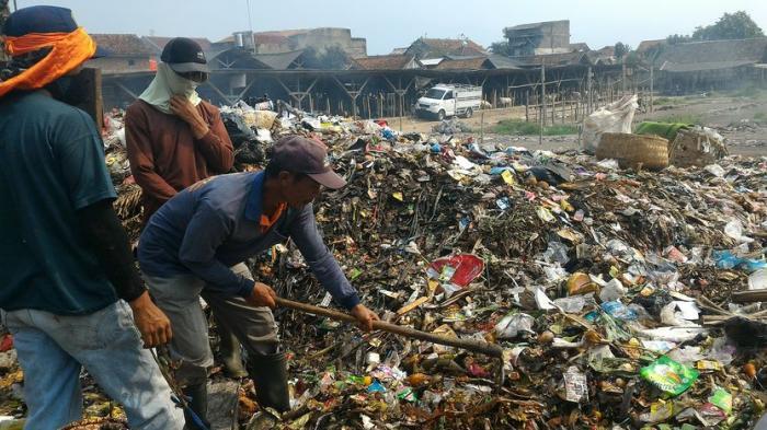 Tenaga Kerja Kontrak UPTD Pasar Banjaran mengangkut sampah dari TPS ke bak penampungan sampah di Pasar Banjaran, Jumat (22/5/2015).