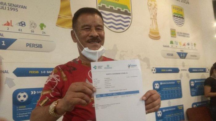 Komisaris PT PBB, Umuh Muchtar, menunjukkan surat keterangan setelah menjalani vaksinasi Covid-19 di Graha Persib, Jumat (19/3/2021).