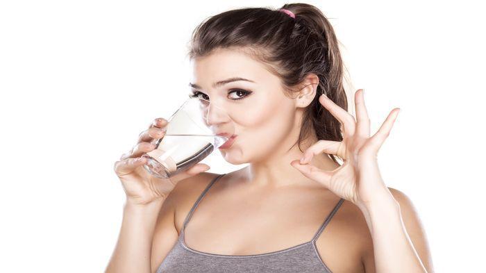 Wanita minum air putih.