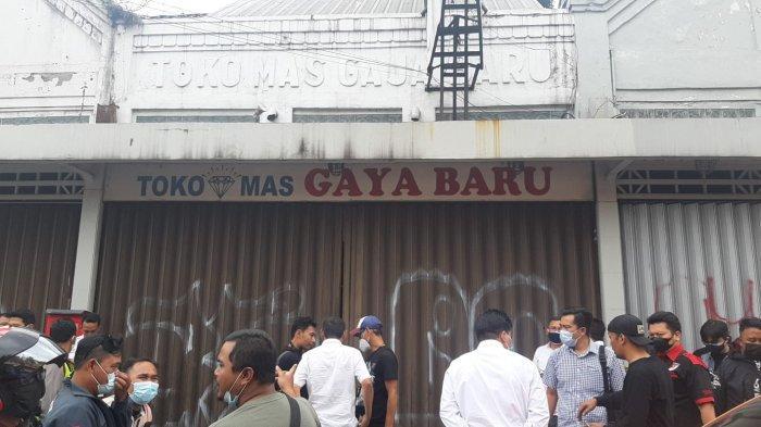Warga dan polisi berkumpul di Toko Mas Gaya Baru.
