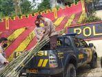 aipda-citro-di-atas-mobil-patroli-sedang-menurunkan-bambu-di-polsek-sukaresmi.jpg