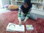 gita-27-seorang-pustakawan-sedang-menunjukkan-beberapa-buku-favorit-anak-anak-di-pustakalana_20171206_173411.jpg