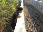 mamat-40-petani-asal-desa-wanakerta-kecamatan-cibatu-memeriksa-saluran-irigasi.jpg