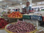 pedagang-sayuran-saat-menunggu-pembeli-di-kiosnya-di-pasar-pagi.jpg