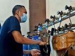 pekerja-toko-alat-medis-sedang-mengisi-ulang-tabung-oksigen.jpg