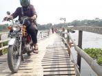pengendara-sepeda-motor-menyeberangi-jembatan-kayu-di-atas-waduk-saguling.jpg