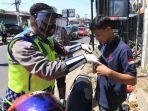 personel-polresta-bandung-memasangkan-masker-kepada-pengguna-sepeda-motor.jpg