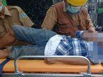petugas-mengevakuasi-jenazah-soleh-55-yang-meninggal-dunia-seusai-bertransaksi.jpg