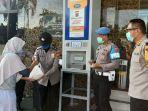 sejumlah-polisi-saat-membantu-masyarakat-mengambil-beras-di-atm-beras.jpg