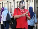 seorang-penumpang-dengan-mengenakan-masker.jpg