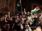 seorang-pria-mengibarkan-bendera-palestina-dan-yang-lain-menunjukkan-tanda-v.jpg