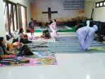 wanita-mengenakan-mukena-sedang-menjalankan-ibadah-salat-di-sebuah-gereja.jpg