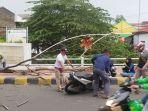 warga-menolong-pengendara-sepeda-motor-yang-tertimpa-pohon.jpg