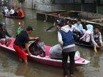 warga-naik-perahu-untuk-melintasi-genangan-banjir.jpg