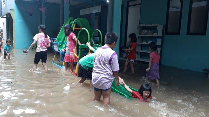 Anak-anak warga Kebon Pala korban banjir luapan Kali Ciliwung saat bermain perosotan di Jatinegara, Jakarta Timur, Rabu (23/6/2021).