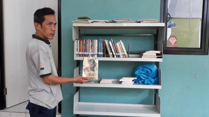 Kabul Arifin (48), warga Kebon Pala korban banjir luapan Kali Ciliwung saat menunjukkan perpustakaan mini yang dibangun Bazis DKI Jakarta di Jatinegara, Jakarta Timur, Rabu (23/6/2021).