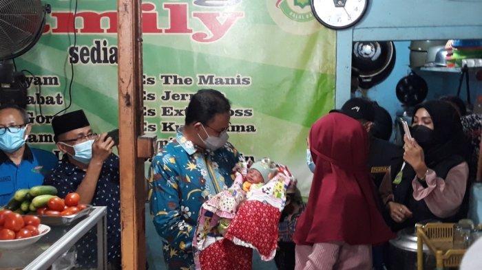 Gubernur DKI Jakarta Anies Baswedan menimang bayi Permata Annisa Nusantara. Permata merupakan cucu Takuri (45), pemilik Warteg Family di Matraman, Jakarta Timur, yang didatangi Anies pada Kamis (14/10/2021).