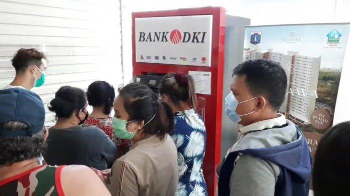 Antrean pencairan BST di ATM Bank DKI Pasar Induk Beras Cipinang, Pulogadung, Jakarta Timur, Senin (19/7/2021)