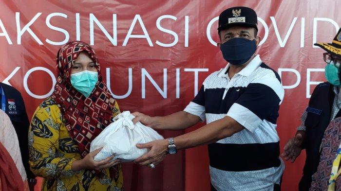 Wali Kota Jakarta Timur Muhammad Anwar saat menyerahkan bingkisan sembako untuk pemulung peserta vaksinasi Covid-19 di Cakung, Sabtu (4/9/2021).