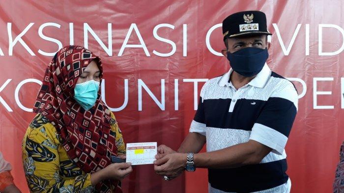 Wali Kota Jakarta Timur Muhammad Anwar saat menyerahkan kartu jadwal dosis dua untuk pemulung peserta vaksinasi Covid-19 di Cakung, Sabtu (4/9/2021).