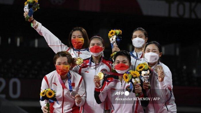 Apriyani Rahayu dari Indonesia (ke-3 dari kanan) dan Greysia Polii dari Indonesia (ketiga dari kiri) berpose dengan medali emas bulu tangkis ganda putri mereka di sebelah Jia Yifan dari Tiongkok (kedua dari kiri) dan Chen Qingchen (kiri) dari Tiongkok dengan medali perak dan Kim So-yeong dari Korea Selatan (2 kanan) dan Kong Hee-yong (kanan) dari Korea Selatan dengan medali perunggu mereka pada upacara selama Olimpiade Tokyo 2020 di Musashino Forest Sports Plaza di Tokyo pada 2 Agustus 2021.