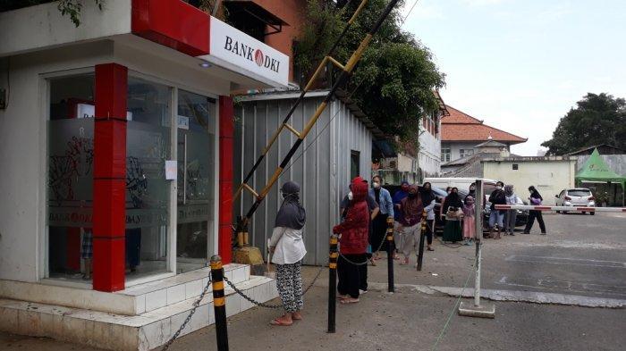 Antrean warga yang hendak mengambil BST sebesar Rp 600 ribu di ATM Bank DKI Jakarta, Pasar Ciracas, Jakarta Timur, Selasa (20/7/2021).