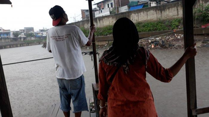 Azis (50) sedang duduk di bagian belakang perahu sembari memegang ponsel pada Rabu (4/11/2020).