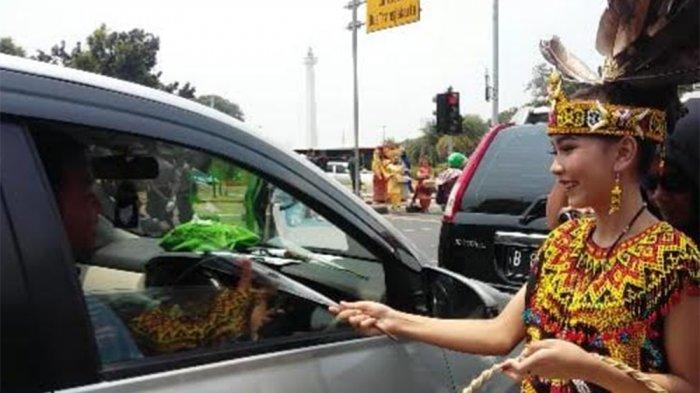 Puluhan Perempuan Berpakaian Adat Bagikan Ratusan Bunga Mawar kepada Pengendara
