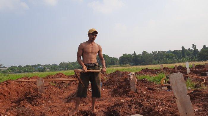 Bahrudin (32), tukang gali kubur di TPU Padurenan Bekasi yang memiliki badan atletis bak model, Senin (10/5/2021).