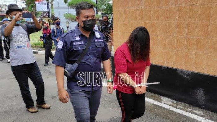 BY, muncikari prostitusi online menutupi wajahnya dengan rambut saat digiring polisi ke sel tahanan Polres Blitar Kota, Rabu (7/4/2021). (surya.co.id/samsul hadi)