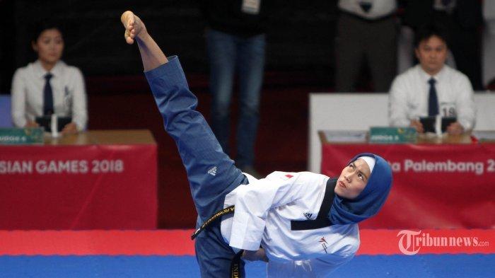 Atlet taekwondo Indonesia Defia Rosmaniar memperagakan jurus pada nomor poomsae pada pertandingan babak 16 besar Asian Games 18, di JCC Jakarta, Minggu (19/8/2018). Defia Rosmaniar mengalahkan atlet taekwondo asal Hong Kong, Ka Yiu Wong.