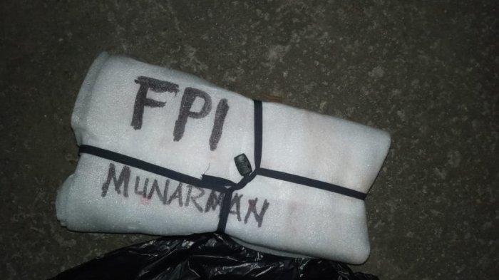 Benda mencurigakan bertuliskan FPI Munarman di depan pintu warung, Senin (5/4/2021).