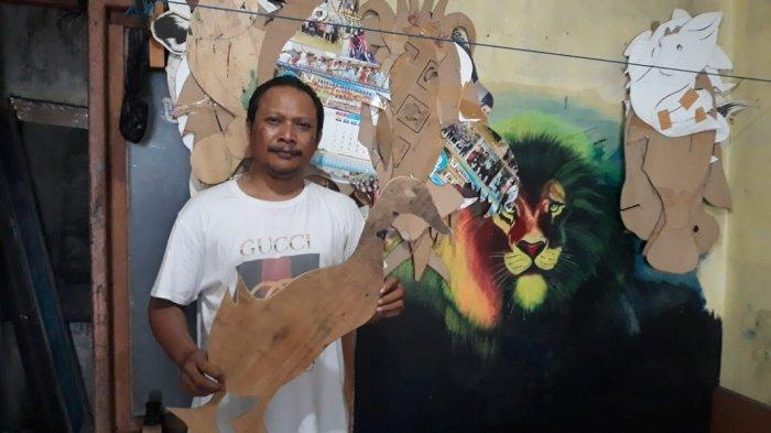 Sosok Hartono, pelukis spanduk pecel lele sedang memegang cetakan kardus berbentuk hewan untuk dilukis di spanduk pada Sabtu (20/2021).