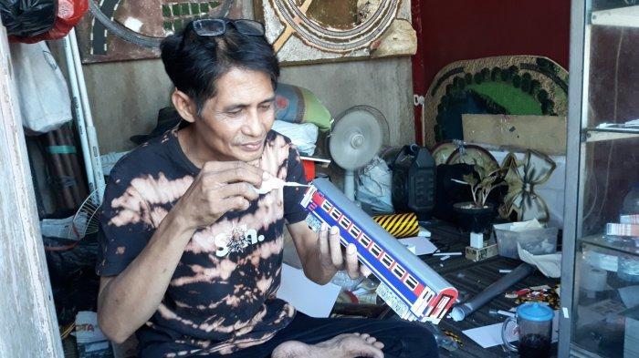 Iskandar sedang membuat miniatur kereta dari bahan pvc di kiosnya pada Selasa (8/9/2020).