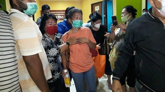 Istri Praka Martinus, Ledy Harti Simamora (baju oranye) saat proses pengambilan jenazah di RS Polri Kramat Jati, Jakarta Timur, Kamis (25/2/2021).