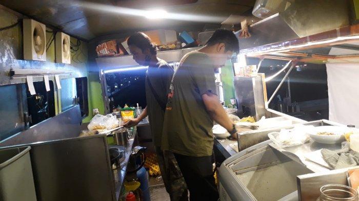 Dua karyawan Mie Aceh Kring-kring sedang memasak pesanan pengunjung di dalam dapur bus antik pada Senin (21/12/2020).