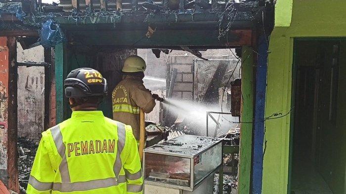 Petugas pemadam kebakaran berjibaku memadamkan api yang membakar kontrakan di Jalan Inspeksi Kali Sunter, RT 007 RW 04 Kelapa Gading Barat, Kelapa Gading, Jakarta Utara, Kamis (25/2/2021).