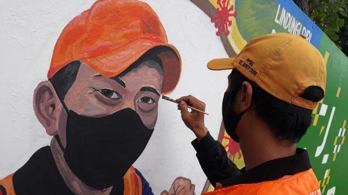 Petugas PPSU Bukit Duri, Edi Gunawan sedang melukis wajah rekan sesama PPSU di Jalan KH Abdullah Syafei, Tebet, Jakarta Selatan pada Selasa (4/5/2021).