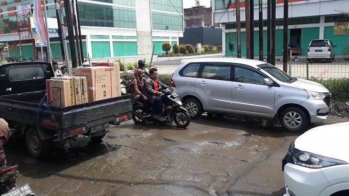 Kondisi Jalan Pejuang Lingkar Utara Kota Bekasi rusak usai terendam genangan air banjir.