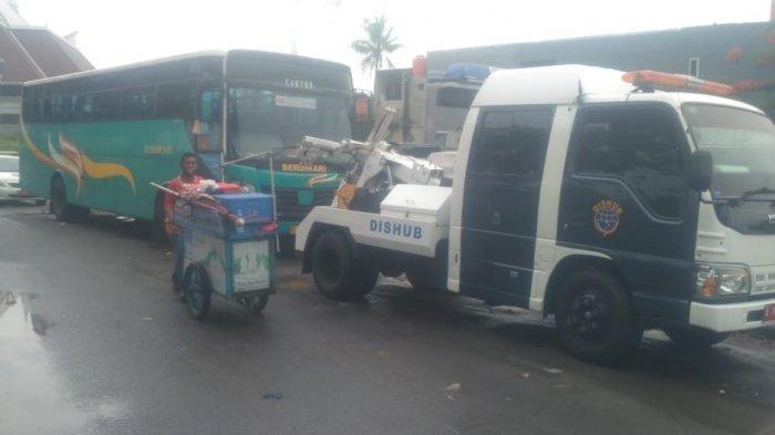 Truk kontainer yang parkir sembarangan di di bahu jalan sekitar Masjid KH Hasyim Asyari, Cengkareng, Jakarta Barat, diderek petugas Dishub.