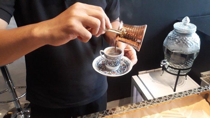 Pelayan menuangkan gelas tembaga berisi kopi ke cangkir pada Jumat (8/1/2021).